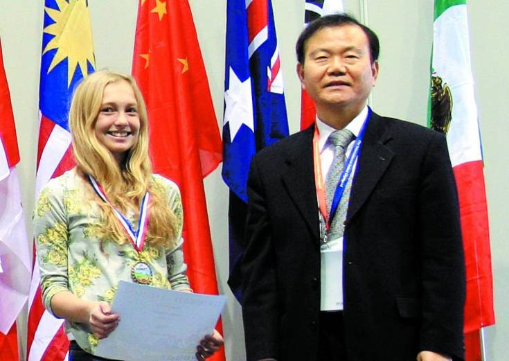 Gold medalist Haley Steinke, left, and Professor Jong-Hwan Kim of South Korea, founder of the International Robot Olympiad take a moment together.