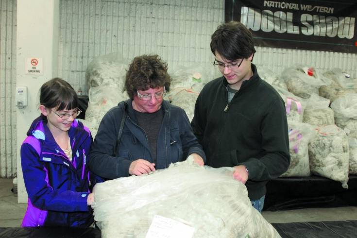 The Younger family, left to right, Mady, Holly and Matthew, check out one of the entries in the Jan. 9 wool show at the National Western Stock Show. The Elbert County family didn't have an entry in the show but, since they are now raising sheep, they came to learn as much as they could about wool.