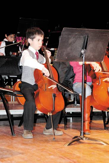 Aidan Johnson plays the cello during the Jan. 12 Strings Attached recital held at the Englewood Middle School Auditorium.