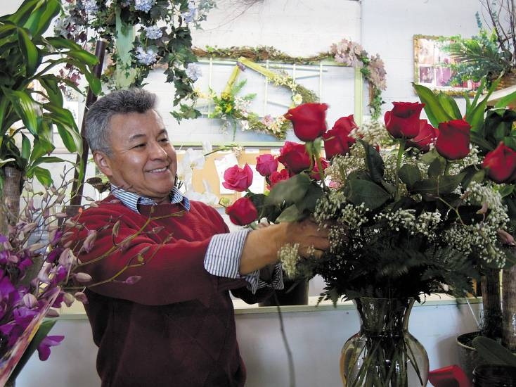 Franklin Mera works on a flower arrangement in his shop, Artistic Flowers & Gifts, last week. Mera began preparing for the busiest day of the year for him, Valentine's Day, weeks ago.