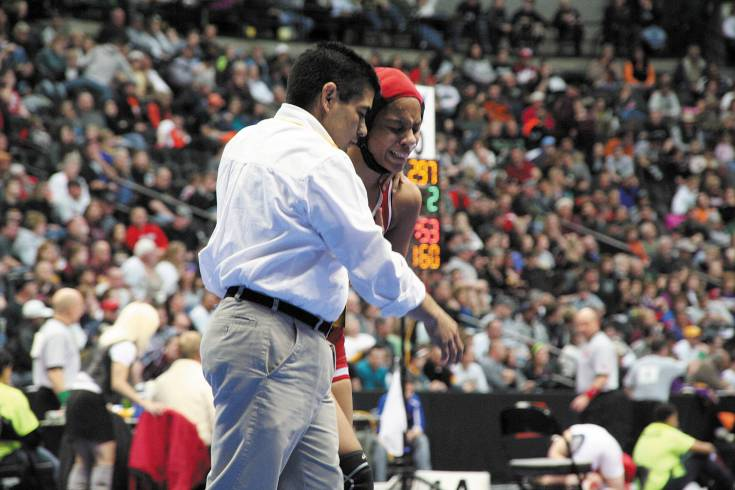 Denver East's Maya Nelson is consoled by her coach after her tough quarterfinal loss Friday night at the Pepsi Center.