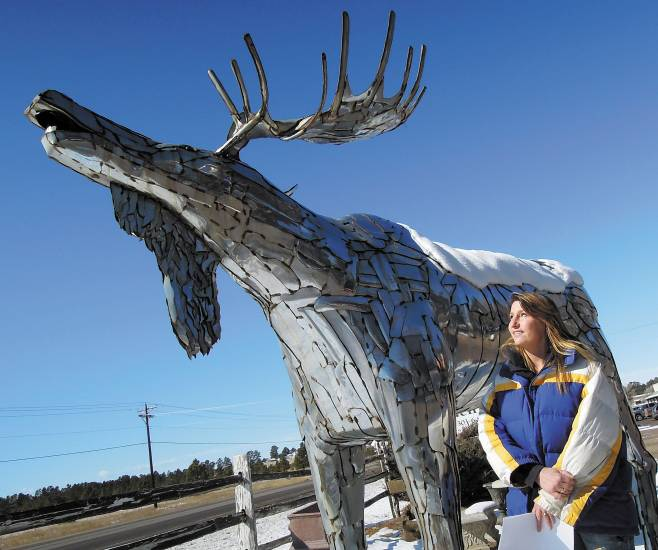"Kelly Bonds, who together with her husband Jim, owns and operates Holly Acres Garden Center and Nursery, admires Elizabeth artist Mike Lawrence's ""metal moose."""