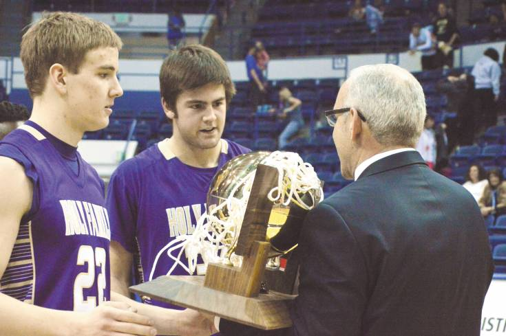 Holy Family senior David Sommers, left, and senior Devlin Granberg, middle, accepts the championship trophy from Colorado High School Activities Association commissioner Bud Ozzello after defeating Pagosa Springs March 15 at the Air Force Academy's Clune Arena.