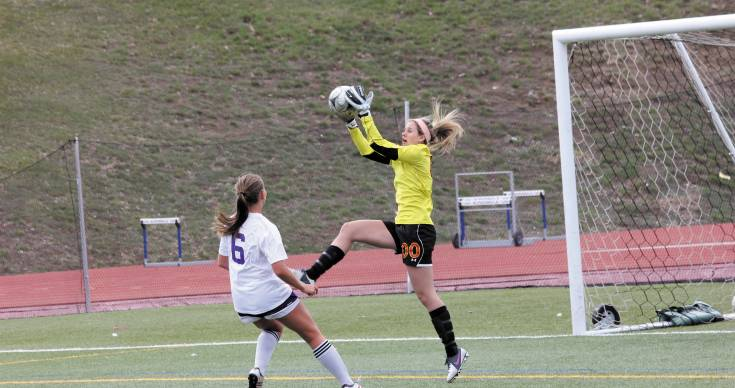 Castle View goalie Danielle Williams (00) goes up to catch the ball and keep it away from Littleton's Abby Newby (6) during the April 1 game. It was a defensive battle that ended in a scoreless tie. Photo by Tom Munds