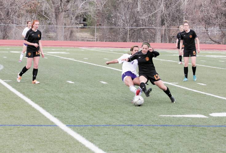 Castle View's Erynn Hargrave (16)  and Littleton's Julie Stauffer (7) crash to the ground battling for the ball during the April 1 soccer game. The battle that included two 10-minute overtime periods ended in a scoreless tie. Photo by Tom Munds