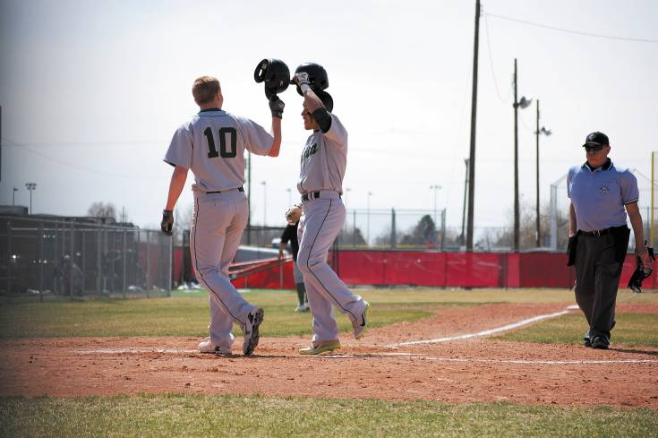 Mountain Vista's Tyler Tullis (10 ) taps helmets with Dylan Formby after Formby hit his third home run of the season April 5. Vista went on to beat host Brighton 5-4.