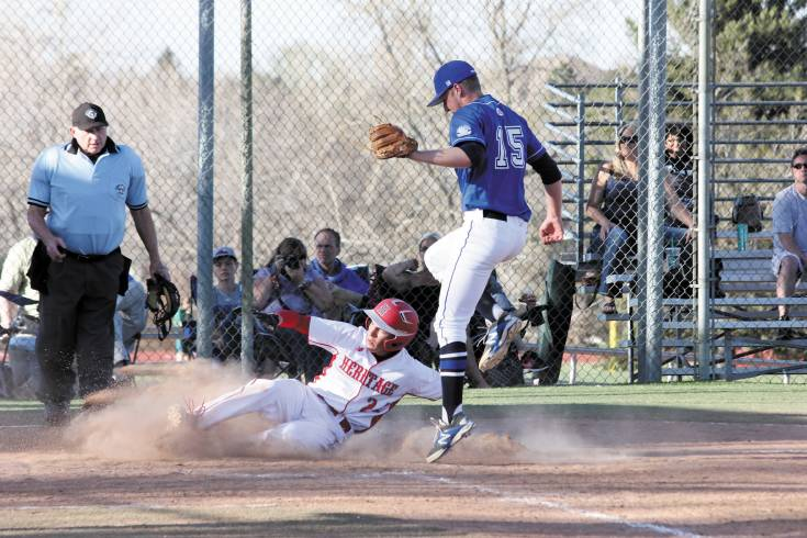 Heritage sophomore Billy Moreland slides into home as Legend's Zacki Viaanderen (15) jumps over him during the April 11 game. The run Moreland scored helped the Eagles win the game, 13-11. Photo by Tom Munds
