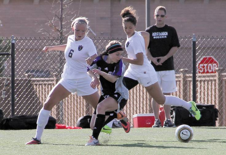 Douglas County's Kate Leachman, center, fights for the ball against Rock Canyon's Alex Vidger, left, and Maddie Brown, right, April 17. The Jaguars got the better of the Huskies in the Continental League battle, 3-0.