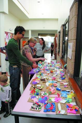 Art teacher Donna Knox points out students artwork at the Lake George Charter School�s Soup�er Art Show held on Apr. 15. Over 100 people from the community came out to raise funds for the school�s art program.