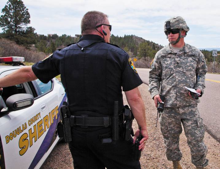 Douglas County Sheriff's deputy Dean Harris chats with Staff Sgt. Ragnar Schuett with the Colorado National Guard during an interagency wildfire evacuation drill near and in the Happy Canyon subdivision in Castle Pines on May 3.