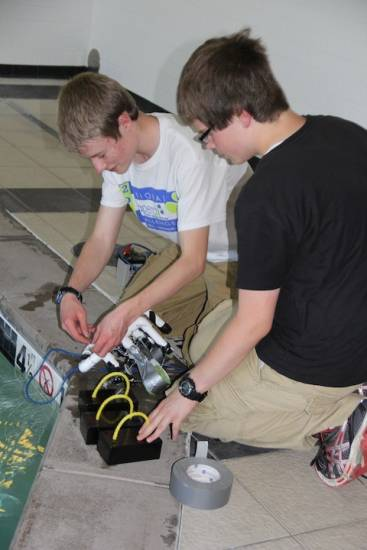 Engineers Kevyn Kelso and Danny Stappenbeck work on a duct tape adjustment to their underwater robot.