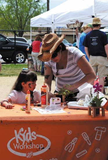 Felicia Kruger shows her daughter, Miliana, how to build a plant holder during the Sustain Arvada Festival.