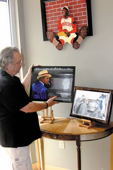 Artist Kyle Banister holds his artwork of Satchel Paige at the piano. Banister created it and other works of members of the Negro Baseball League that will be used as part of a television feature about the league's museum in Kansas City.