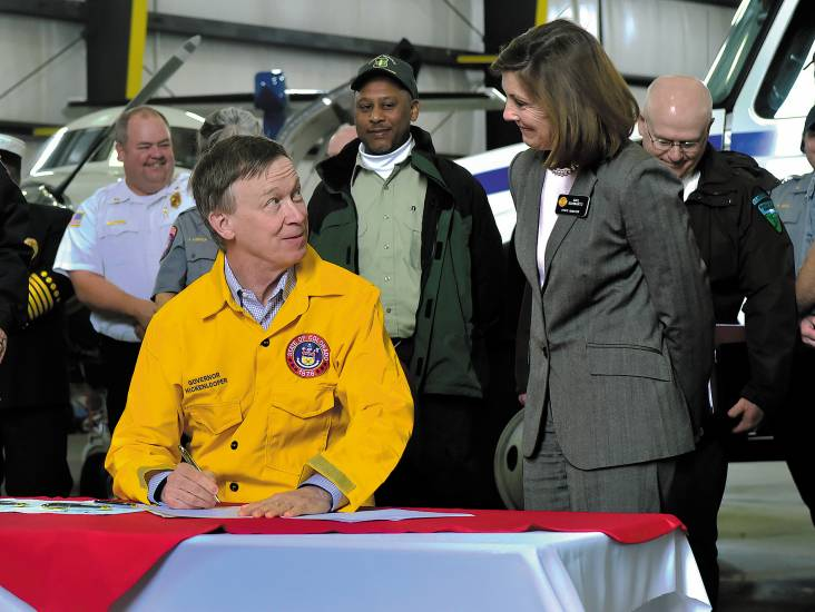 Gov. John Hicklenlooper prepares to sign into law three new bills that will help Colorado prepare for an �unpredictable� wildfire season, as Sen. Gail Schwartz looks on. The governor, along with several state and federal fire agency representatives gathered Monday, May 12 at Centennial Airport to sign the legislation which will authorize nearly $20 million to expand the state's firefighting fleet.