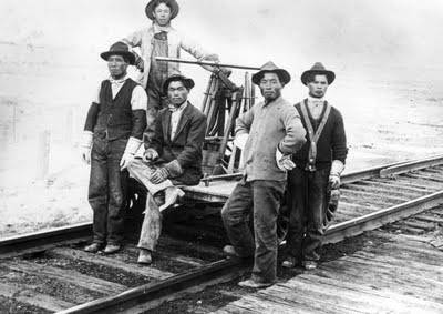 Five Japanese rail workers pose around a rail handcart. Photo taken between 1900 and 1910.