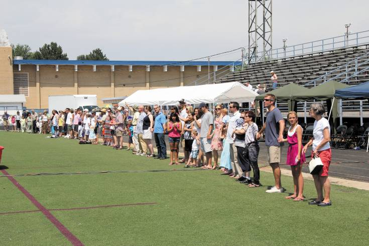 Those attending the 2012 Unite Englewood worship service join hands and form a circle to pray for their neighbors, the city and its leaders. This year's Unite Englewood event will be May 25 on the high school baseball field.
