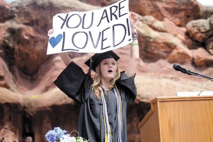 Class speaker Hannah Lamieux pulls out a sign during her speech at Highlands Ranch High School's graduation ceremony at Red Rocks Amphitheater on May 21.