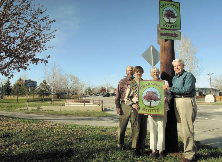 (From left) Larry Borger, Cole Hancock, Mary Gardinier and Dick Dugdale display the sign the city presented to Gardinier in honor of her late husband, Vaughn, who created the city's Crabapple Trail.  File photo