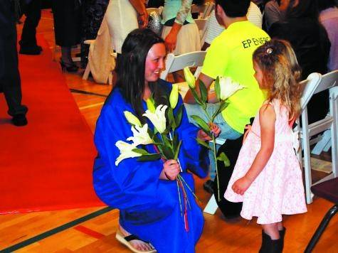Cripple Creek-Victor High School graduate Karense Marie Zaccardi, left, gives her fist lily to her 4-year-old cousin Anabelle. It took a while for Principal Trudy Vader to get the students and audience members back to their seats so the commencement exercises could be completed.