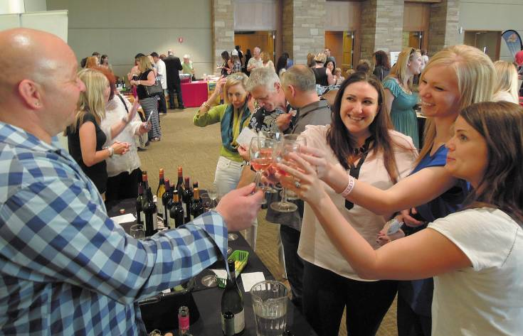 From left, Keith Dougherty from Beverage Distributors Company toasts Marissa Firstenburg, Desiree Pezzulo and Jess Allen during The Wildlife Experience's art sale and wine tasting June 6. Photo by Chris Michlewicz