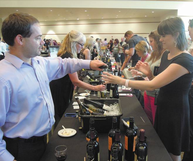 "Erik Nielsen from Aurora-based Wine Cru pours a ""Seven Deadly Sins"" riesling for Parker resident Maddie Stanforth at The Wildlife Experience's annual Art & Wine event June 6. Photo by Chris Michlewicz"