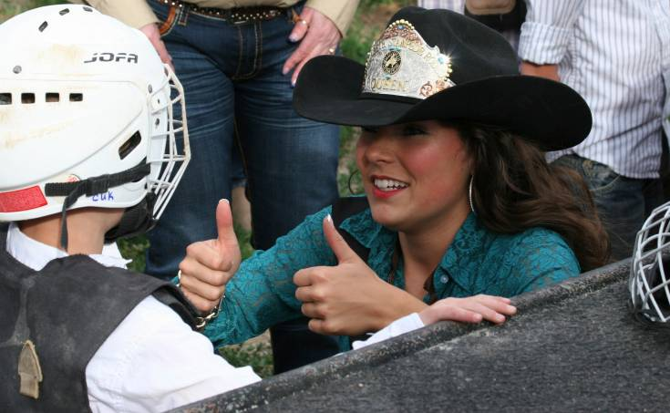 Nadia Postek, the 2015 Elizabeth Stampede Queen, helps equip mutton busters during the Cowboy Up in Kiowa Rodeo on June 27.