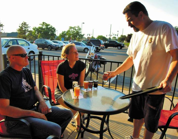 Three Freaks owner Jeff Atencio, right, serves tasters to Highlands Ranch residents and first-time customers Dan and Sue Dolquist July 2.