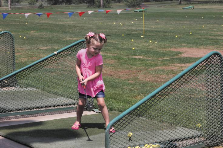 Avery Lenertz, 3, hits a ball off the tee on the driving range at the Broken Tee at Englewood Golf Course. The Highlands Ranch girl and her brothers Logan and Jake attended the July 2 barbecue and activities culminating this year's Hole-N-One Youth Golf Program.