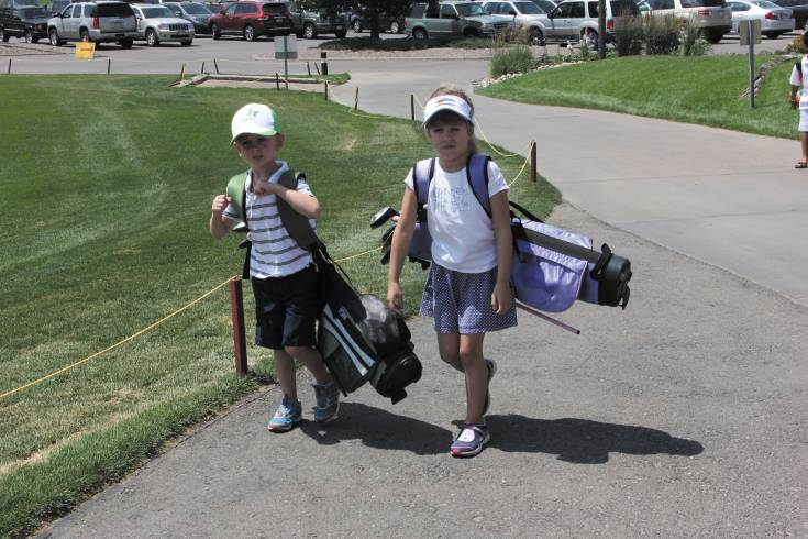 Benjamin Behan, left, and his sister Delilah have their clubs with them as they attend the July 2 celebration culminating the Hole-N-One Youth Golf Program. The Littleton residents were among about 400 boys and girls who took part in the group golf lesson program at Broken Tee at Englewood Golf Course.