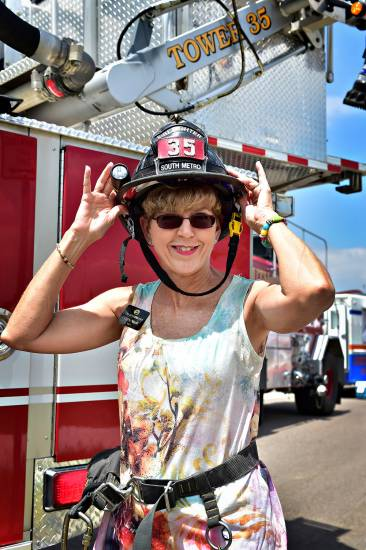Centennial Mayor Cathy Noon dons a firefighter�s helmet before taking a ride in South Metro Fire Rescue Authority�s tower truck. The Mayor and SMFRA were on hand Saturday, July 12 at the Centennial Artisan and Farmer�s Market held at Centennial Center park.