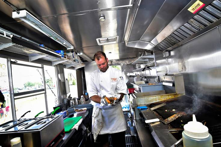 Chef Tim Martin sizes up a Colorado-style cheese steak sandwich at the Centennial Artisans and Farmers market, Saturday, July 12 at Centennial Center Park. Martin, who owns Gusto�s Kitchen, was one of several area food trucks featured at the monthly event.