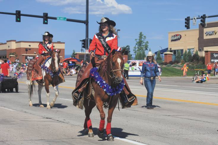 Maria Orlova, front, the 2014 Douglas County Fair and Rodeo queen, rides in the Highlands Ranch Fourth of July parade.