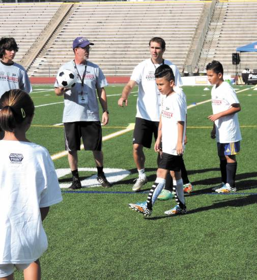 Brian Mullan of the Rapids helps direct campers at the start of the July 24 Biddle Soccer Pro Camp at Littleton High School.