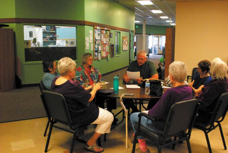 Arvada Senior Liaison Officer, Tom VanderVeen, sits with a group of seniors at the Apex Community Recreation Center in Arvada to update them about the latest scams targeting the senior population.