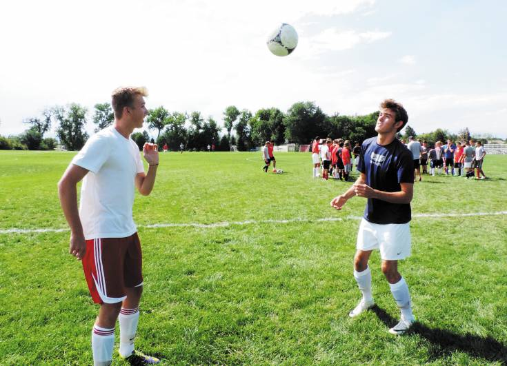 Heritage senior Chase Breslaw, right, heads the ball to his sophomore brother Noah, left, during practice Aug. 13.