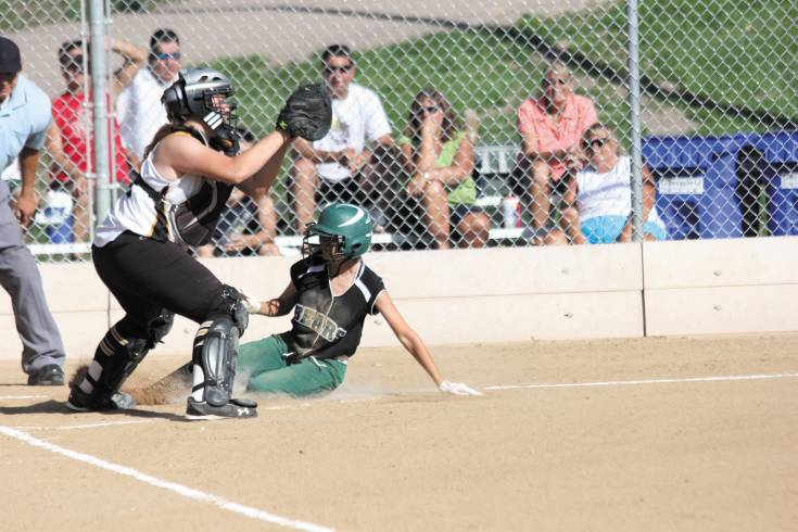Arapahoe catcher Cheyenne Serrano catches the ball to late to tag he sliding Bear creek runner at the plate during the Aug. 20 non-league softball game. The run was important as the Bears went on to edge the Warrors, 5-4.