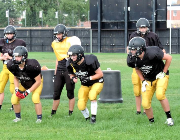 Arapahoe High players prepare Aug. 25 for the Warriors' season-opening game Aug. 29 against Legend at Parker's Sports Authority Field.