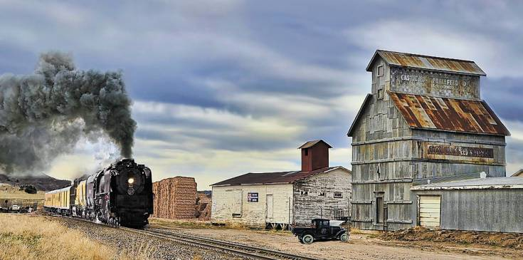 """Steam in Castle Rock,"" by Ken Smith, shows Union Pacific No. 844, celebrating the 150th anniversary of the railroad, next to the Castle Rock Grainery."