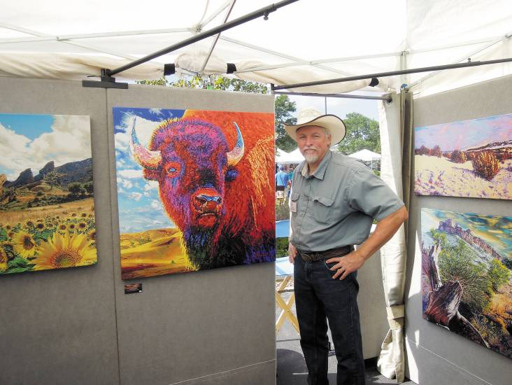 Darien Bogart poses with his nature-inspired oil paintings Sept. 6 at Colorado ArtFest in Castle Rock.