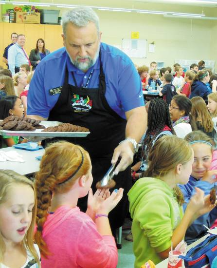 Douglas County School Board president Kevin Larsen doles out whole-grain, double-chocolate-chip cookies to sixth-graders at Parker's Mammoth Heights Elementary on Colorado Proud Day Sept. 10. Photo by Jane Reuter