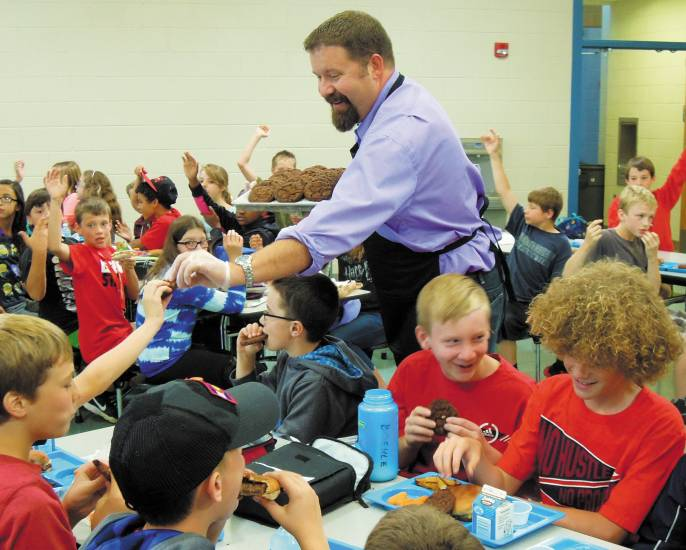 Parker Mayor Mike Waid doles out whole-grain double chocolate-chip cookies to sixth-graders at Mammoth Heights Elementary on Sept. 10's Colorado Proud Day. Photo by Jane Reuter