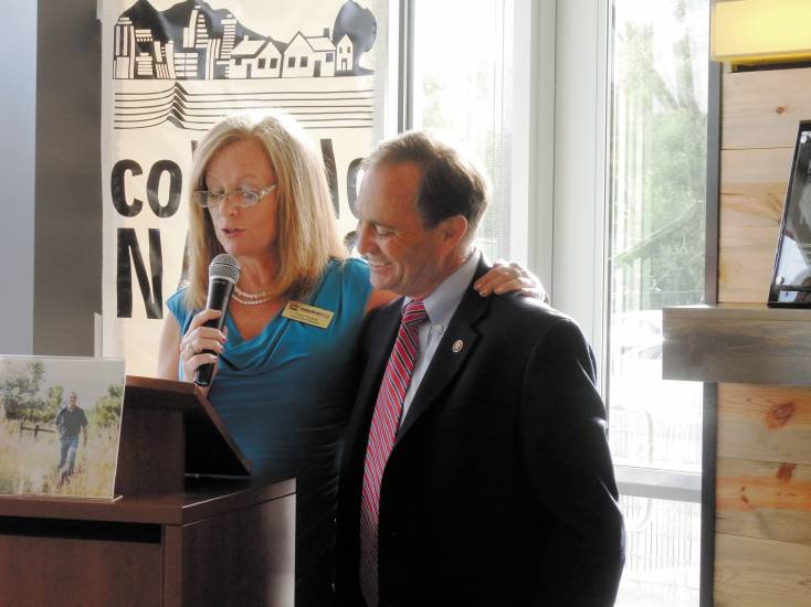 "Rep. Ed Perlmutter listens as Tami Fischer, executive director and CEO of Metro West Housing Solutions, reads a proclamation giving him the Colorado chapter of National Association of Housing and Redevelopment Officials' (NAHRO) ""Legislator of the Year"" award."
