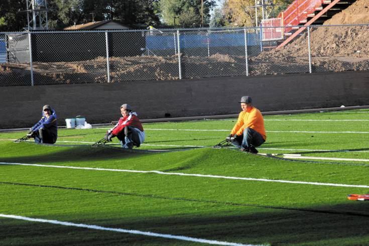 Workers stretch the artificial turf on the new practice field located north of Englewood High School Stadium. The new field will be available for school and recreational department use as well as for use by the public.