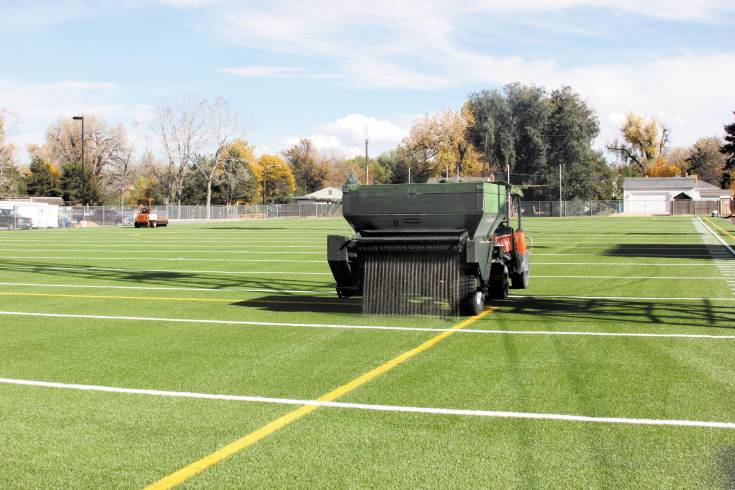 A tractor spreads sand and small rubber pellets as part of the installation process of the artificial turf on the practice field north of Englewood High School Stadium. The field was made possible by a partnership between the city and the school district.