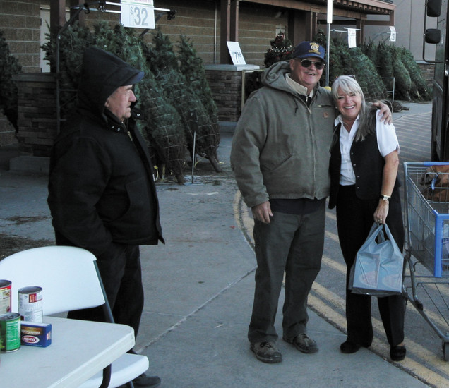 Cyndy Collaro donates bags of food and gets a hug from the American Legion's John Guttenberg. AL Calvin Pagel is at left.