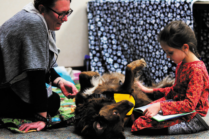 Minnie enjoys getting her belly scratched while listening as Ella Bergstrom, right, reads her book with Raylene Kaufman, pet therapy reader with Pet Partners.