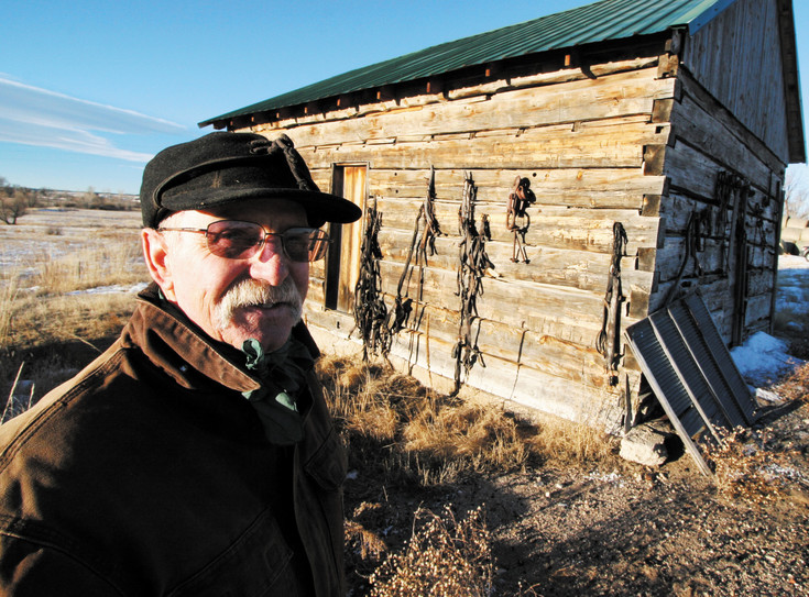 Charlie Carnahan stands recently in front of the family's original homestead built in 1862.