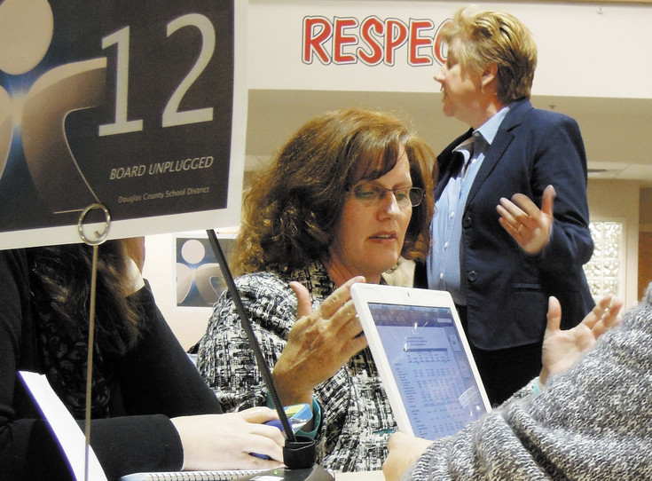 School board member Judi Reynolds talks with community members during a March 2014 Board Unplugged meeting at Cimarron Middle School. Some say communication has been a problem between the school district and parents. File photo