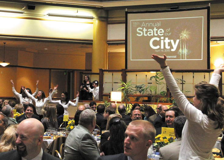 The Boulder Flash Mob, in white with arms in the air, surprised guests during Centennial's State of the City with a quick dance routine. Centennial Mayor Cathy Noon wanted to lighten the mood of the event, and introduced 2014 as the year of great performances.