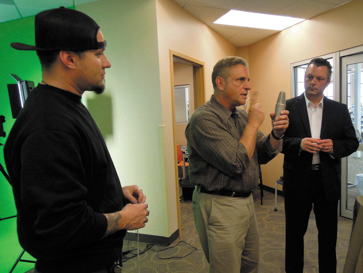 Norm Silver, coach and curriculum development specialist for Warrior Voices, demonstrates the proper distance from the mic while recording voiceovers as veteran Chad Ritter, left, and Warrior Voices Founder/CEO Rob Reese look on. Photo by Chris Michlewicz